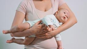 Schönes Baby in ihren Mutter-Armen lizenzfreies stockfoto