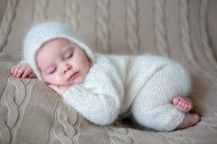 Schönes Baby im Weiß strickte die Stoffe und Hut und schlief Lizenzfreie Stockfotos