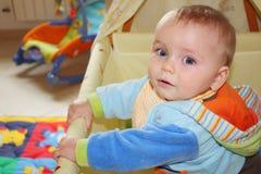 Schönes Baby mit einer farbigen Spielanzugreihe, die in seinem Feldbett steht Stockfotografie