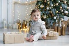 Schönes Baby sitzt nahe dem Weihnachtsbaum und den Geschenkboxen Lizenzfreies Stockbild