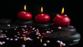 Schönes Badekurortkonzept von Kerzen, Zensteine mit Tropfen Stockbild