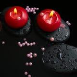 Schönes Badekurortstillleben von Kerzen, Zensteine mit Tropfen Stockfotos