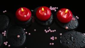 Schönes Badekurortstillleben von Kerzen, Zensteine mit Tropfen Lizenzfreies Stockfoto