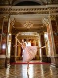 Schönes Ballerinatanzen in einer Arabeskenballetthaltung gegen den luxuriösen Innenraum stockfoto