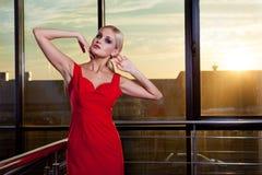 Schönes bezauberndes blondes Mädchen in einem roten Kleid, das nahe Glasschaukasten im Geschäftszentrum aufwirft Sonneneruption i Stockfotografie