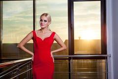 Schönes bezauberndes blondes Mädchen in einem roten Kleid, das nahe Glasschaukasten im Geschäftszentrum aufwirft Sonneneruption i Stockbilder
