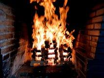 Schönes Bild des bewegenden Feuers in einem Feuer gemacht mit hölzernen Planken im Gitter im Ziegelsteinkamin stockfotos