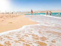 Schönes Bild von den Wellen des ruhigen Sees, die auf dem sandigen Seestrand am hellen sonnigen Tag rollen Perfekter Hintergrund  stockfotos