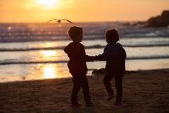 Schönes Bild von zwei Jungen auf dem Strand bei Sonnenuntergang Lizenzfreie Stockbilder