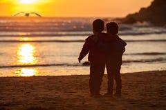 Schönes Bild von zwei Jungen auf dem Strand bei Sonnenuntergang Stockfotos