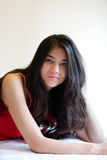 Schönes biracial jugendlich Mädchen, das sich, entspannend hinlegt Stockfotos