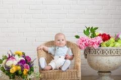 Schönes blauäugiges Baby in einem geflochtenen Stuhl, nahe bei einem Vase Blumen Stockbilder