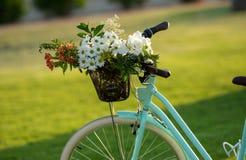 Schönes blaues Fahrrad mit einem Korb von Blumen Stockfoto
