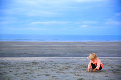 Schönes blond-haariges Mädchen, das auf dem Strand sitzt Lizenzfreie Stockfotos