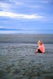 Schönes blond-haariges Mädchen, das auf dem Strand sitzt Stockfotografie