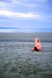 Schönes blond-haariges Mädchen, das auf dem Strand sitzt Stockfotos