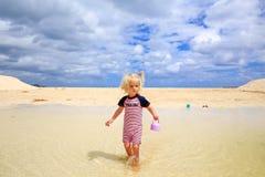 Schönes blond-haariges Mädchen, das auf sandigen Strand geht Lizenzfreies Stockfoto
