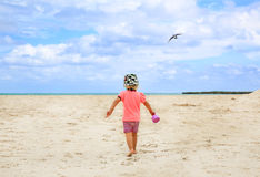 Schönes blond-haariges Mädchen, das auf sandigen Strand geht Stockfotos