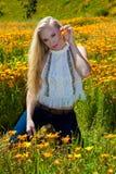 Schönes blondes auf dem Blumengebiet Lizenzfreies Stockbild