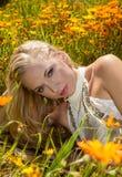 Schönes blondes auf dem Blumengebiet Stockfotografie