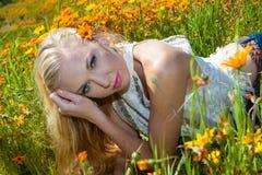 Schönes blondes auf dem Blumengebiet Lizenzfreie Stockbilder
