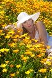 Schönes blondes auf dem Blumengebiet Stockbild