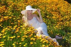Schönes blondes auf dem Blumengebiet Stockfotos