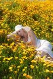 Schönes blondes auf dem Blumengebiet Lizenzfreie Stockfotografie