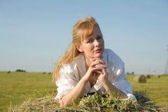 Schönes blondes Bauernmädchen sittitng auf gelbem Heu mit Blumenstrauß Stockfotografie