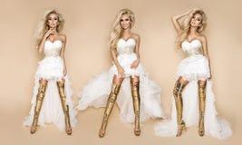 Schönes blondes Brautmodell in einem Hochzeitskleid und erstaunlichen in Goldschuhen stockfoto