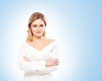 Schönes blondes in den weißen Strickwaren auf blauem Hintergrund Lizenzfreies Stockbild