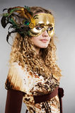 Schönes blondes in der venetianischen Schablone mit Federn Lizenzfreies Stockbild