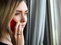 Schönes blondes durchdachtes Geschäftsfraugesprächsmobiltelefon Lizenzfreie Stockfotos