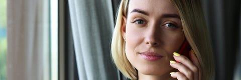 Schönes blondes durchdachtes Geschäftsfraugesprächsmobiltelefon Stockfoto