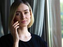 Schönes blondes durchdachtes Geschäftsfraugesprächsmobiltelefon Stockbild