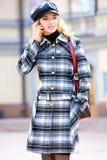 Schönes blondes in einem Mantel spricht am Telefon Stockfoto