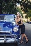 Schönes blondes elegantes Mädchen mit blauem Weinleseauto Stockfotografie