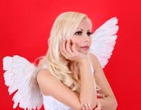 Schönes blondes Engelsmädchen über Rot Lizenzfreie Stockfotos
