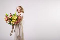 Schönes blondes Frühlingsmädchen mit großem Blumenstrauß blüht Stockfoto