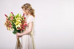 Schönes blondes Frühlingsmädchen mit großem Blumenstrauß blüht Stockbilder