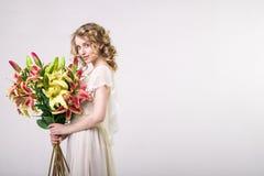 Schönes blondes Frühlingsmädchen mit großem Blumenstrauß blüht Stockfotos