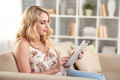 Schönes blondes Frauen-Graseninternet zu Hause Lizenzfreie Stockbilder