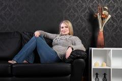 Schönes blondes Frauenhaus auf Sofa im Überbrücker Lizenzfreie Stockbilder