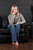 Schönes blondes Frauenhaus sitzt auf ledernem Sofa Lizenzfreie Stockbilder