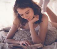 schönes blondes Frauenlesebuch im Bett Entspannendes Konzept Lizenzfreie Stockfotos