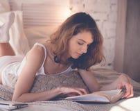schönes blondes Frauenlesebuch im Bett Entspannendes Konzept Lizenzfreie Stockbilder