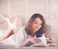 schönes blondes Frauenlesebuch im Bett Entspannendes Konzept Stockbilder
