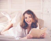 schönes blondes Frauenlesebuch im Bett Entspannendes Konzept Stockfotos