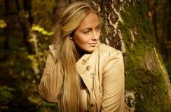 Schönes blondes Frauenporträt im Wald mit grünem und gelbem Baumhintergrund Stockbild