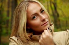 Schönes blondes Frauenporträt im Wald mit grünem und gelbem Baumhintergrund Lizenzfreies Stockfoto